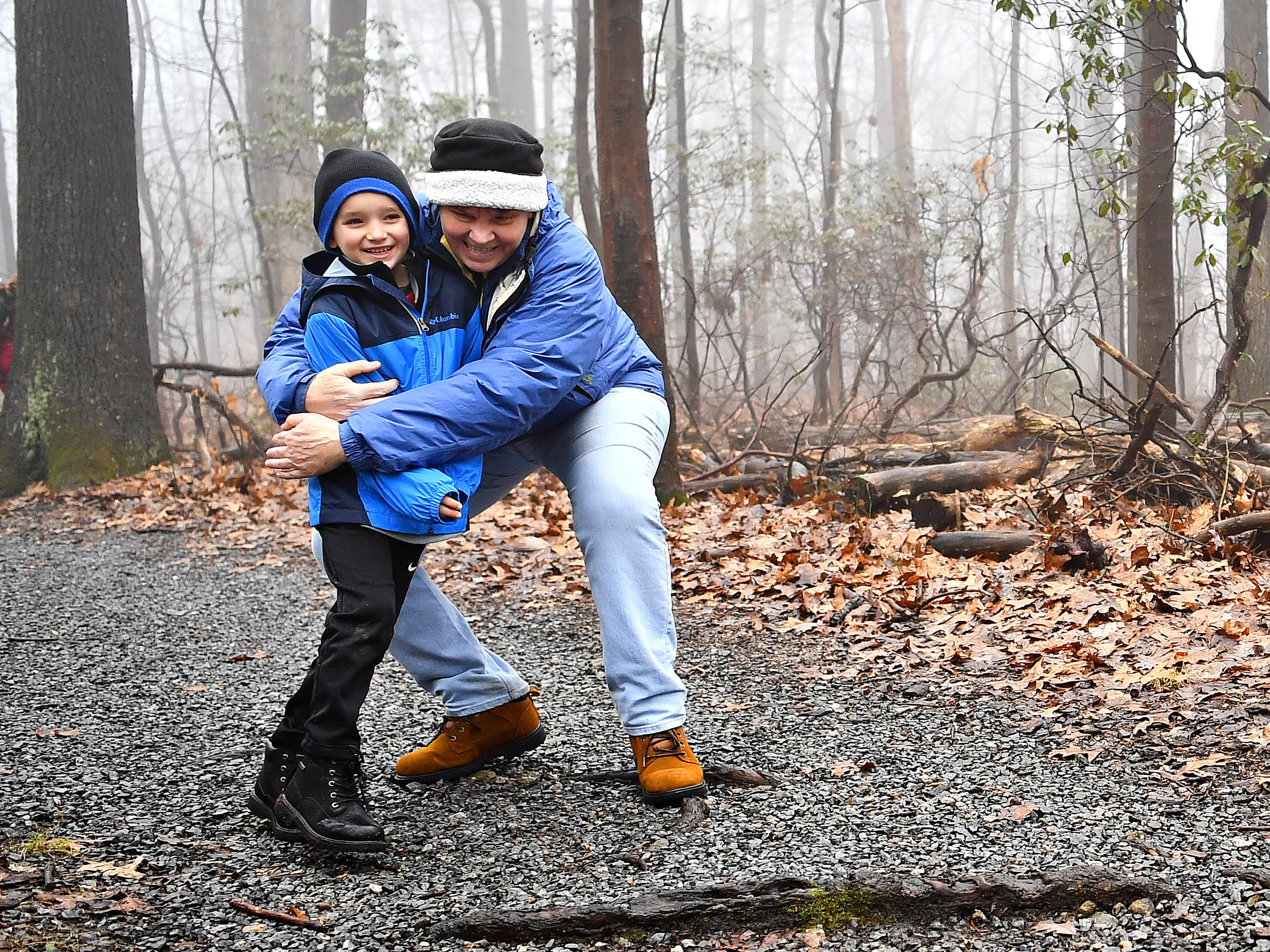 Tanya Merchant, back left, of East Manchester Township, embraces her great-nephew Mason Zercher, 6, during a Marshmallow Hike led by York County Parks Naturalist Kelsey Frey at Rocky Ridge Park in Springettsbury Township, Friday, Dec. 28, 2018. Dawn J. Sagert photo