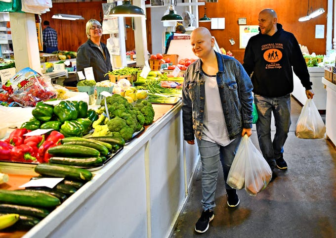 From right, Steve Hill and Katie, both of Manchester Township, walk with their bags of fresh produce and meat while Jami Godfrey, of R.L. Godfrey looks on at Penn Market in York City, Friday, Dec. 22, 2018. Nana's Oven has been in Penn Market since March of 2016. Dawn J. Sagert photo