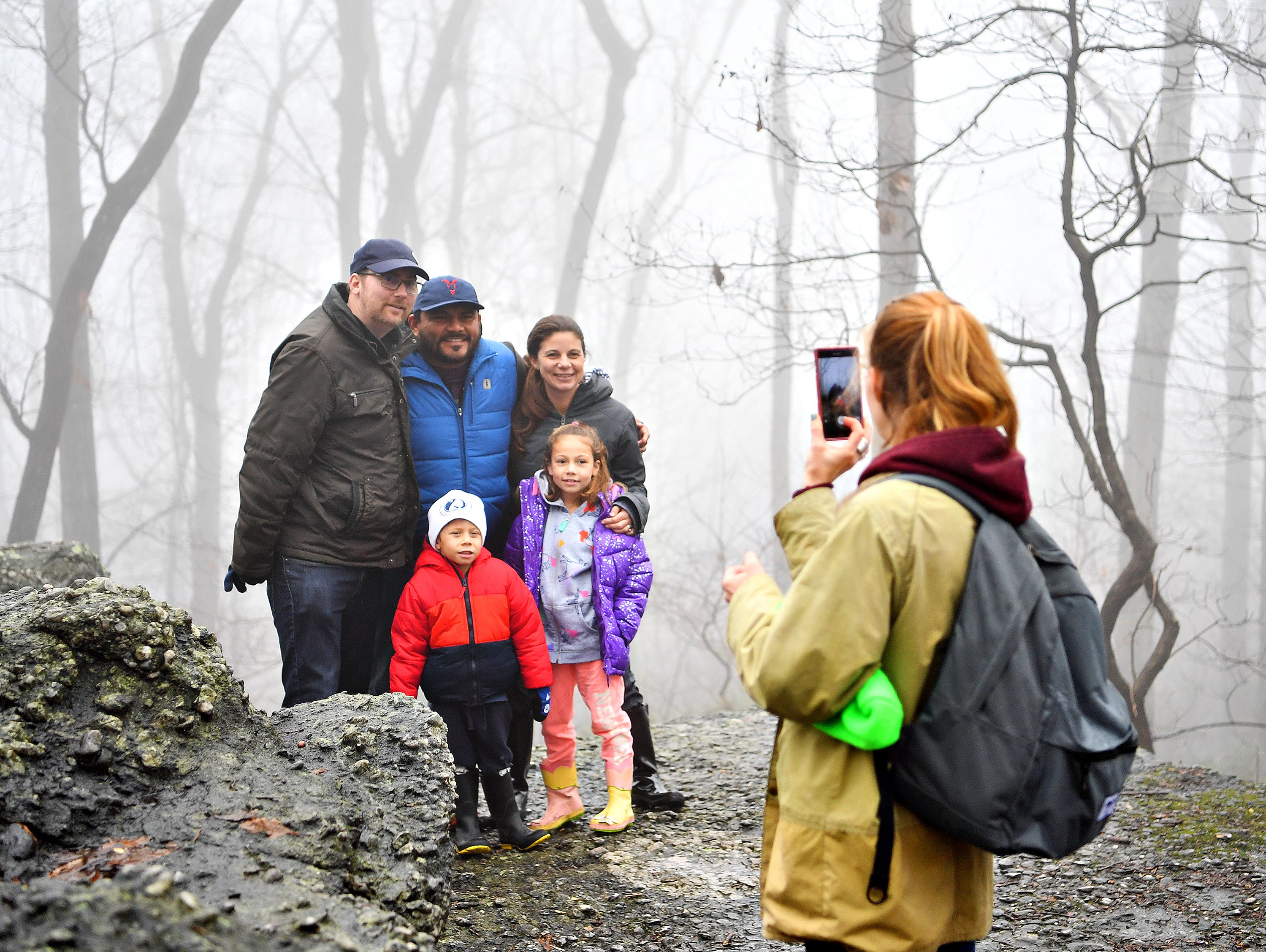 Melanie Butler, right, of Lancaster, photographs family members, clockwise from left, Joel Butler, of Victoria, Canada, Manny Hernandez, Tiffany Butler, Matilda Hernandez, 7, and Tiago Hernandez, 4, all of Yucatan, Mexico, against a backdrop of trees in the fog during a Marshmallow Hike led by York County Parks Naturalist Kelsey Frey at Rocky Ridge Park in Springettsbury Township, Friday, Dec. 28, 2018. Dawn J. Sagert photo