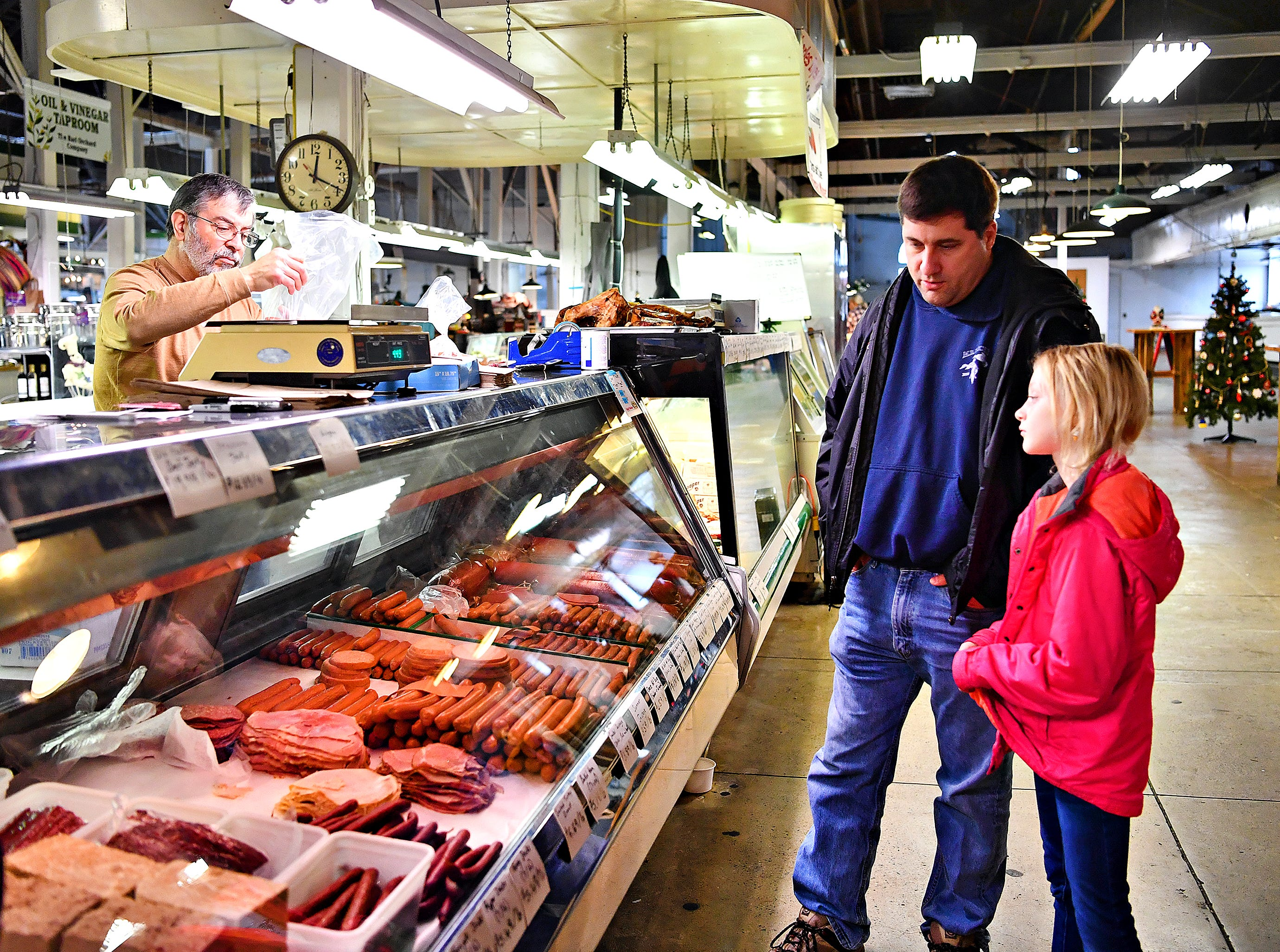 From right, Kearsea Godfrey, 9, and her father Chad Godfrey wait while Matthew Folgleman, of Charles Ilyes Family, Inc., Meats and Produce at Penn Market in York City, Friday, Dec. 28, 2018. Dawn J. Sagert photo