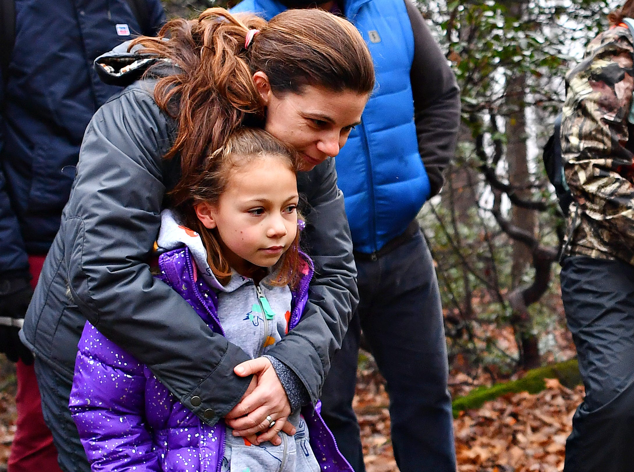 Matilda Hernandez, 7, is hugged by her mother Tiffany Butler, both of Yucatan, Mexico, as York County Parks Naturalist Kelsey Frey leads a Marshmallow Hike at Rocky Ridge Park in Springettsbury Township, Friday, Dec. 28, 2018. Dawn J. Sagert photo