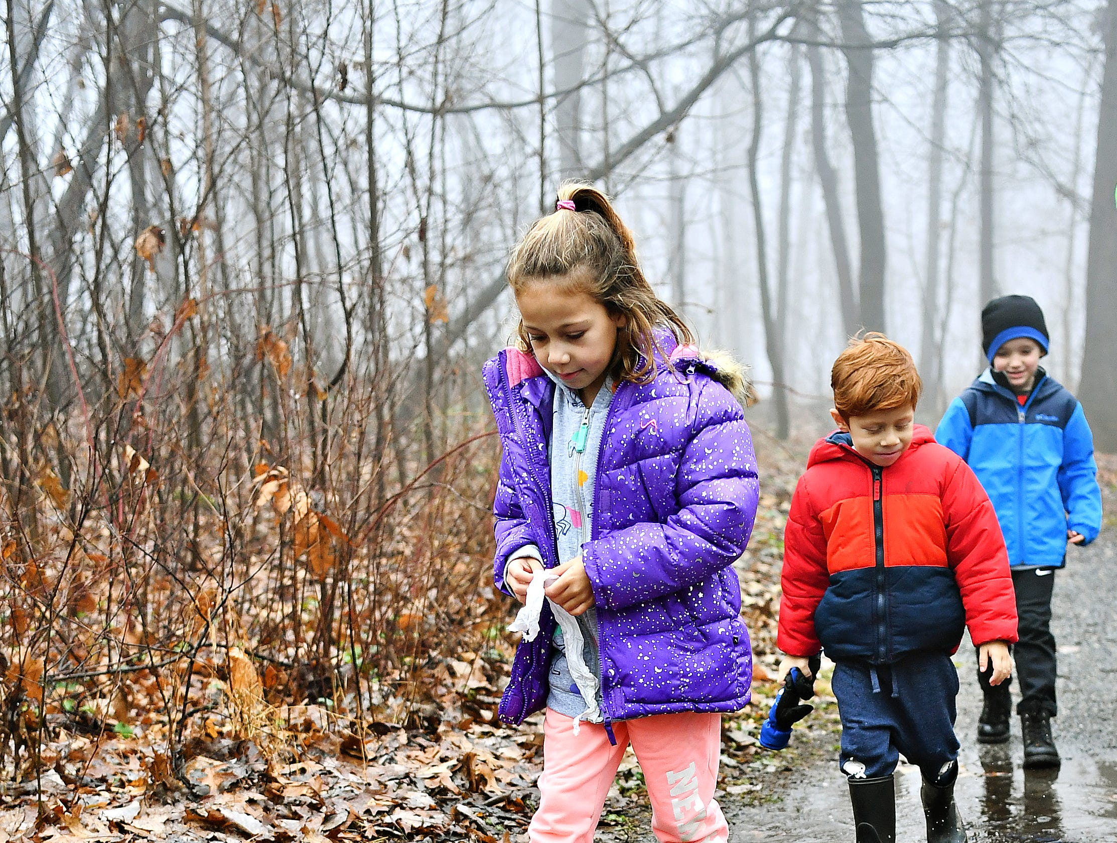 From front, Matilda Hernandez, 7, and her brother Tiago Hernandez, 4, both of Yucatan, Mexico, and Mason Zercher, 6, of East Manchester Township, walk into a puddle on the trail during a Marshmallow Hike led by York County Parks Naturalist Kelsey Frey at Rocky Ridge Park in Springettsbury Township, Friday, Dec. 28, 2018. Dawn J. Sagert photo