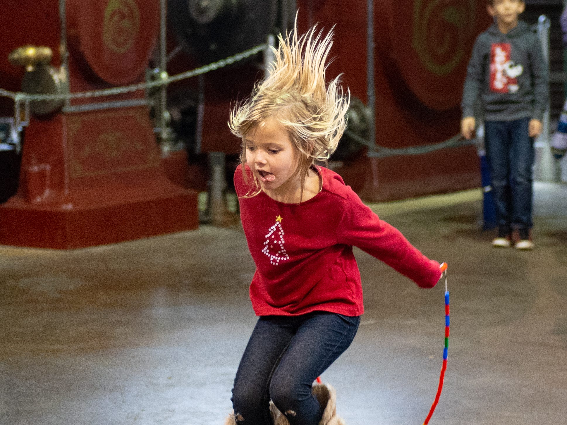 Iola Henz, 5, plays with her new jump rope that she made during family activity day at the Agricultural and Industrial Museum, Friday, December 28, 2018.
