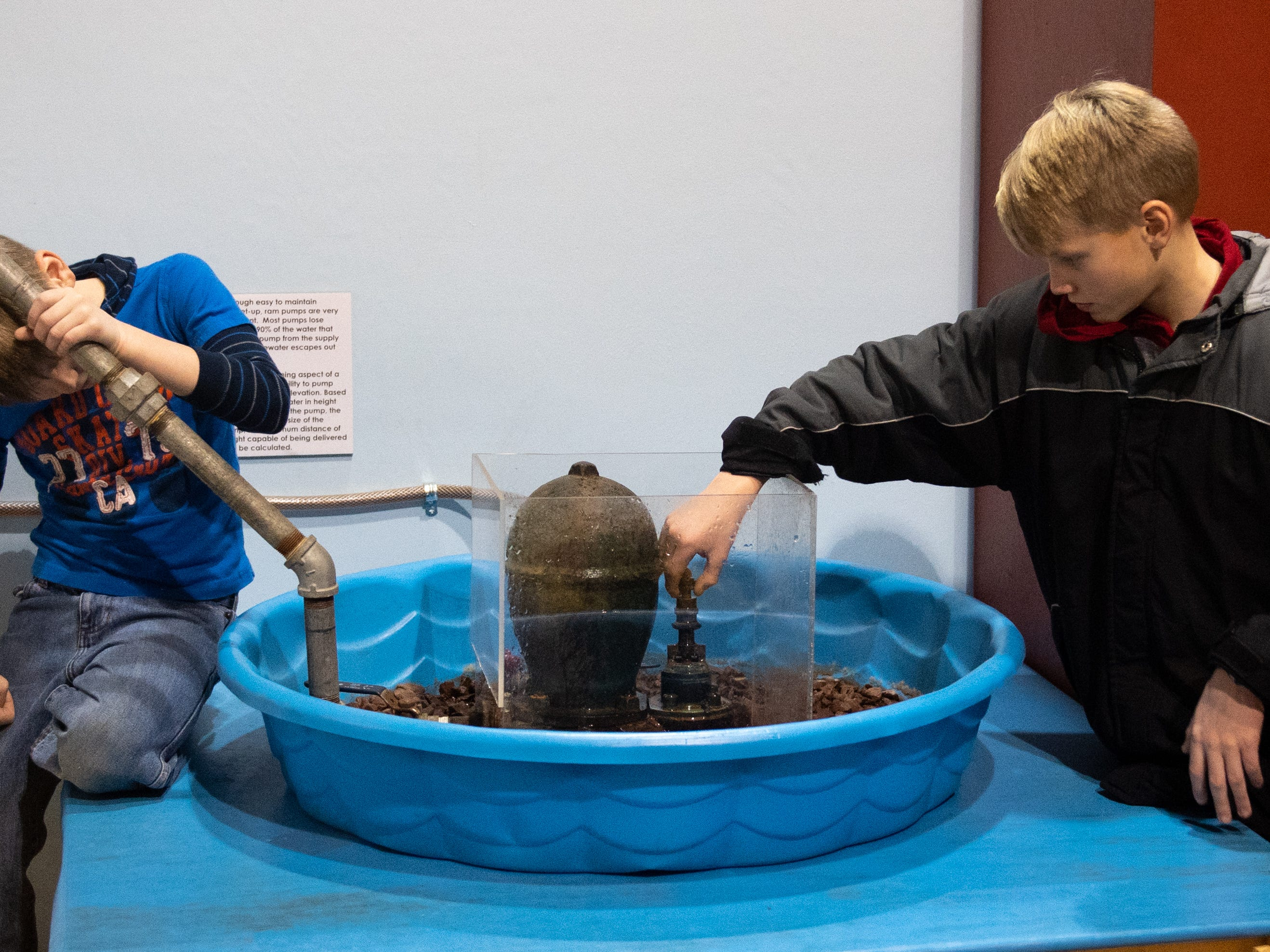 Ewrin Henz, 8, (left) and his brother Emory, 11, (right) of Stewartstown operate a pump during family activity day at the Agricultural and Industrial Museum, Friday, December 28, 2018.