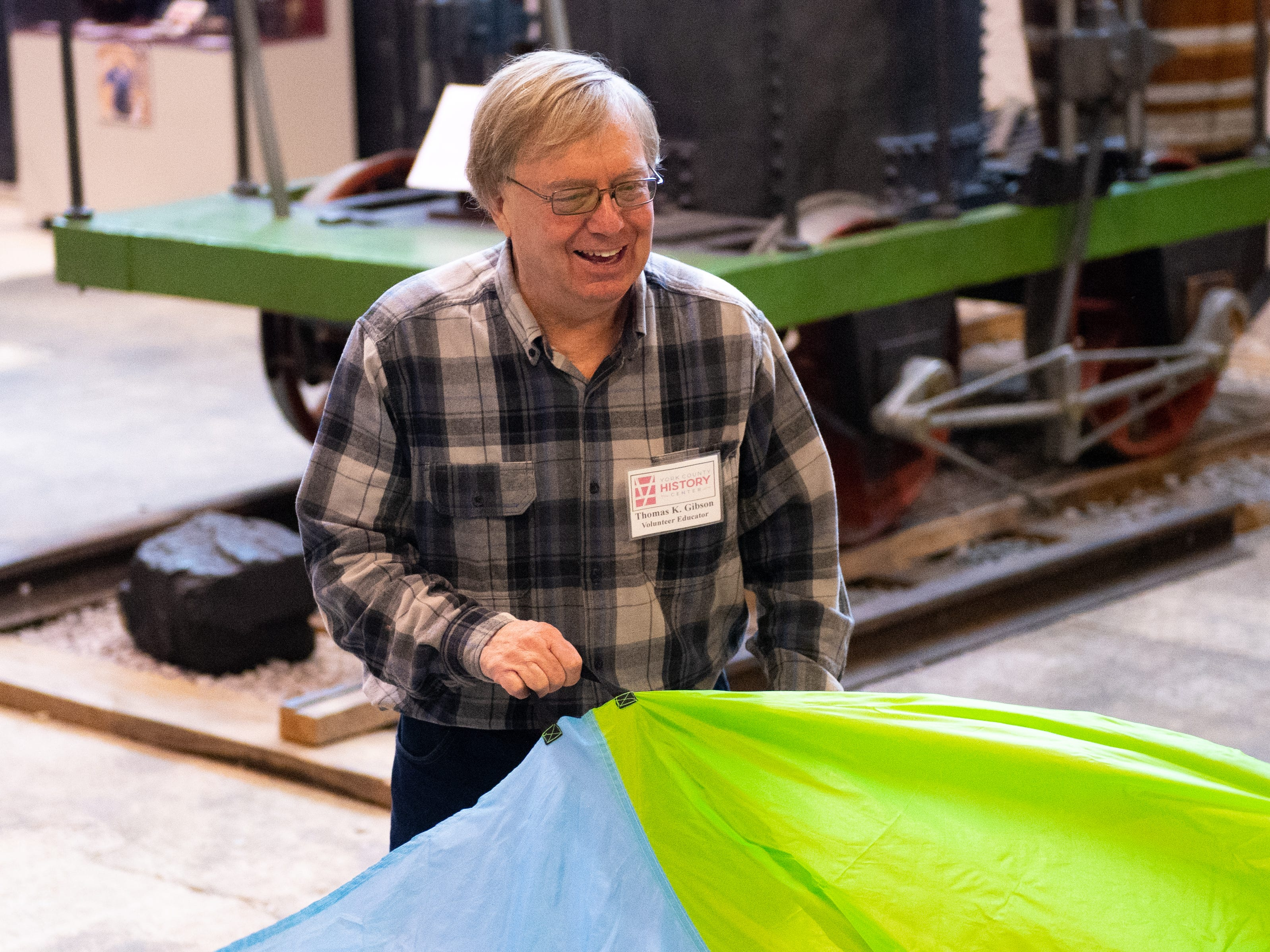 Volunteer Tom Gibson teaches children parachute games during family activity day at the Agricultural and Industrial Museum, Friday, December 28, 2018.