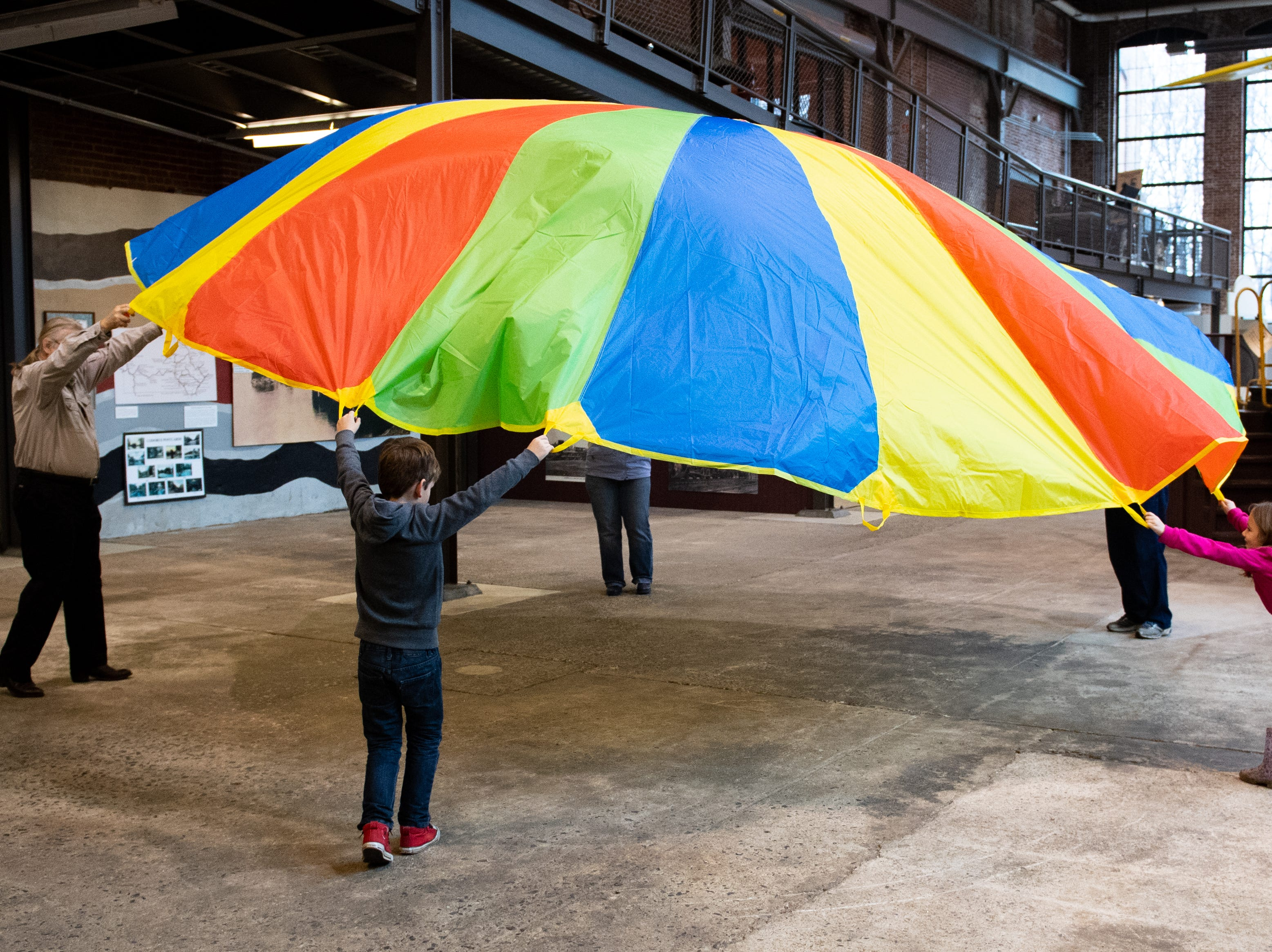 Visitors prepare to run underneath the giant parachute during family activity day at the Agricultural and Industrial Museum, Friday, December 28, 2018.