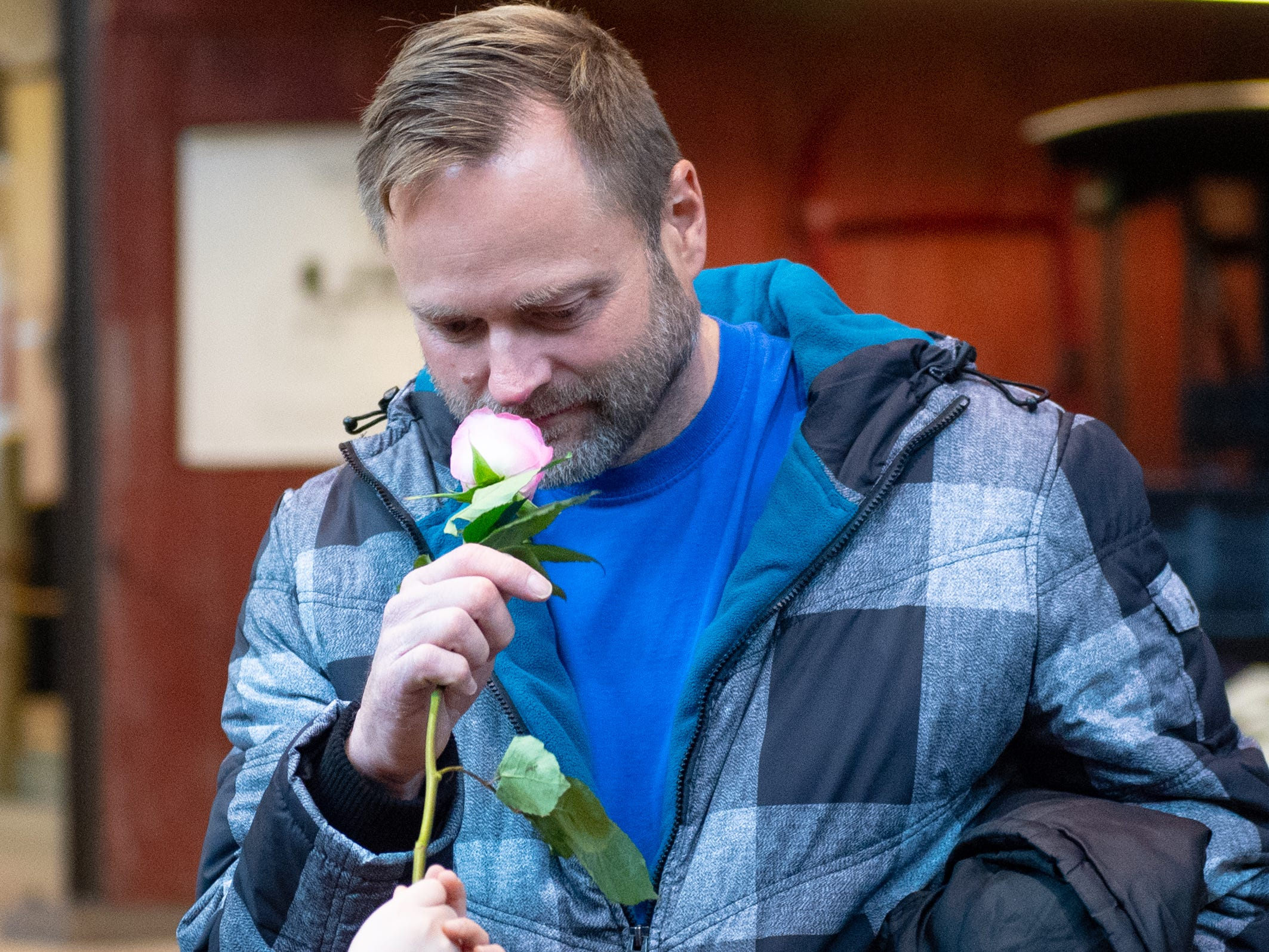 Brian Henz sniffs a flower a the five senses booth, December 28, 2018.