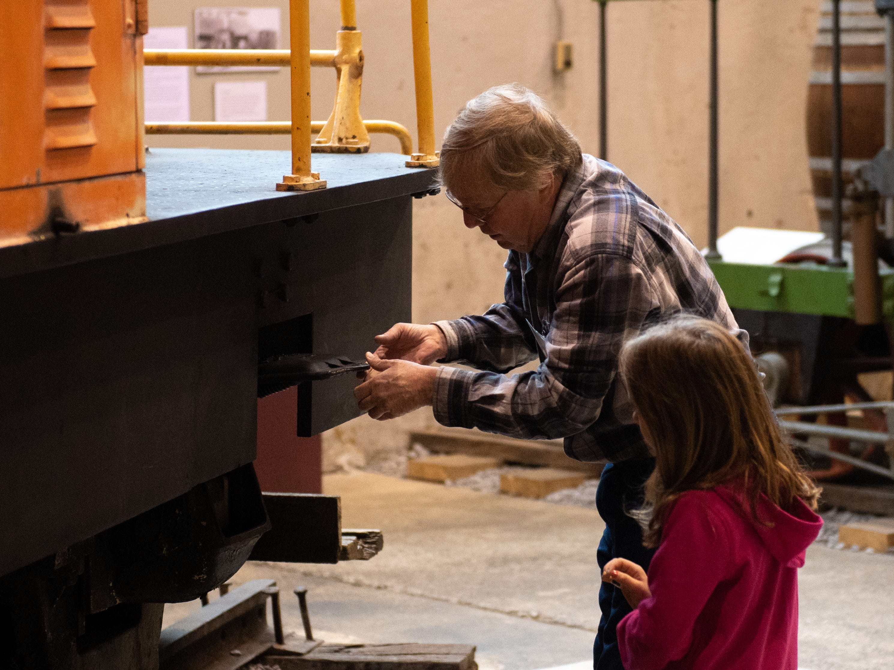 Volunteer Tom Gibson shows Ada Erdenbrack parts of an old train during family activity day at the Agricultural and Industrial Museum, Friday, December 28, 2018.