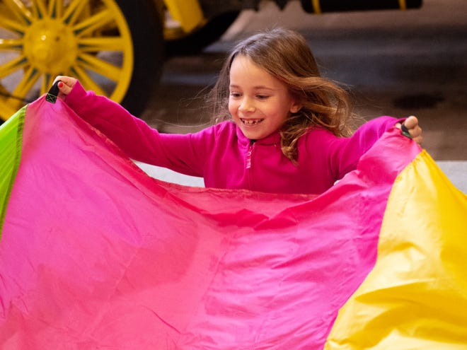 Ada Erdenbrack, 6, from Springrettsbury Township, enjoys learning parachute games during Family Activity Day at the Agricultural and Industrial Museum on Friday.