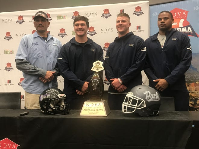 From left, Nevada head coach Jay Norvell, along with senior captains Wes Farnsworth, Ty Gangi, and Malik Reed, pose with the Arizona Bowl trophy Friday in Tucson, Ariz.