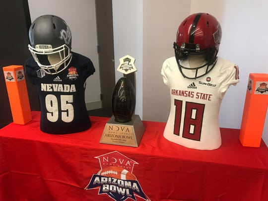 The Arizona Bow trophy is shown with Nevada and Arkansas State jerseys