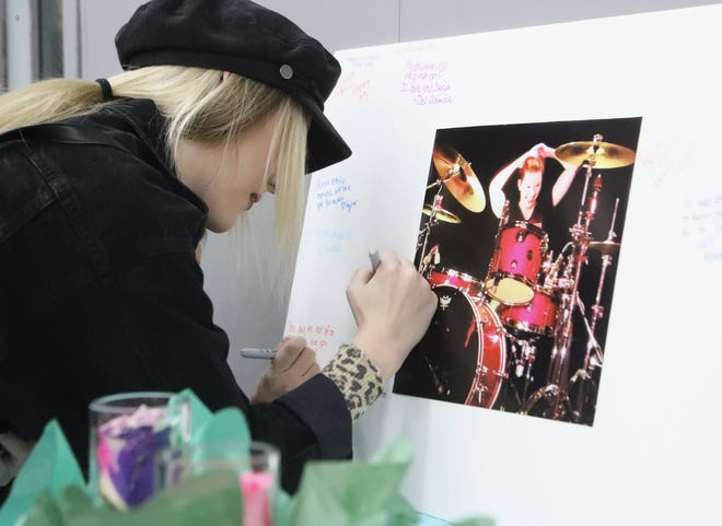 Samantha Hoeft of Redding signs a photo mat dedicated to Foothill High School graduate Sarah Papenheim during a memorial Thursday night at the school. Papenheim was slain Dec. 12 in the Netherlands and her roommate was arrested in the murder.
