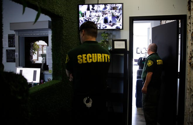 FILE - In this June 27, 2017 photo, two security guards stand watch at a medical marijuana dispensary in Los Angeles, a business conducted mostly in cash. The legal marijuana industry often finds the doors locked at banks, its money unwanted because the drug remains illegal under federal law. California would likely lose money and face insurmountable federal hurdles if it tried to create a state-backed bank for the marijuana industry. That's according to a report released Thursday, dec. 27, 2018, by state Treasurer John Chiang. It puts an end for now to hopes of creating a public bank as California's recreational marijuana market concludes its first year. Chiang is blasting the federal government for keeping marijuana a Schedule 1 drug even though 33 states have legalized it for recreational or medicinal purposes. (AP Photo/Jae C. Hong, File)