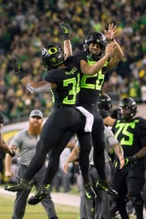 Oregon running back CJ Verdell (34) celebrates with teammate running back Travis Dye (26) on Nov. 17.