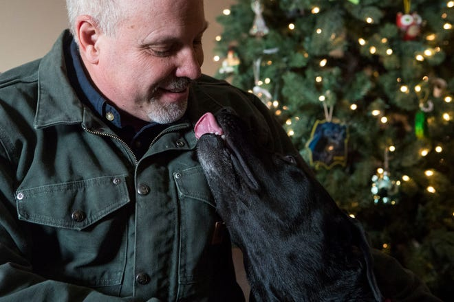 Dan Buehner spends time with his dog, Husker, at his house in Sioux Falls, S.D., Friday, Dec. 28, 2018.