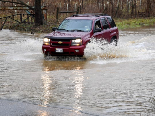 An SUV crosses where water from Christians Creek flows over the paved surface of Christians Creek Road in Augusta County on Friday afternoon, Dec. 28, 2018.