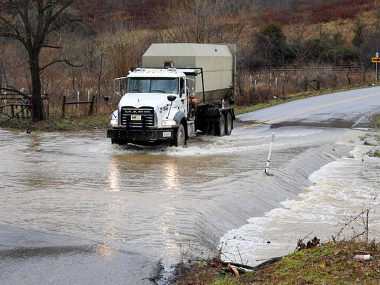A truck crosses where water from Christians Creek flows over the paved surface of Christians Creek Road in Augusta County on Friday afternoon, Dec. 28, 2018.