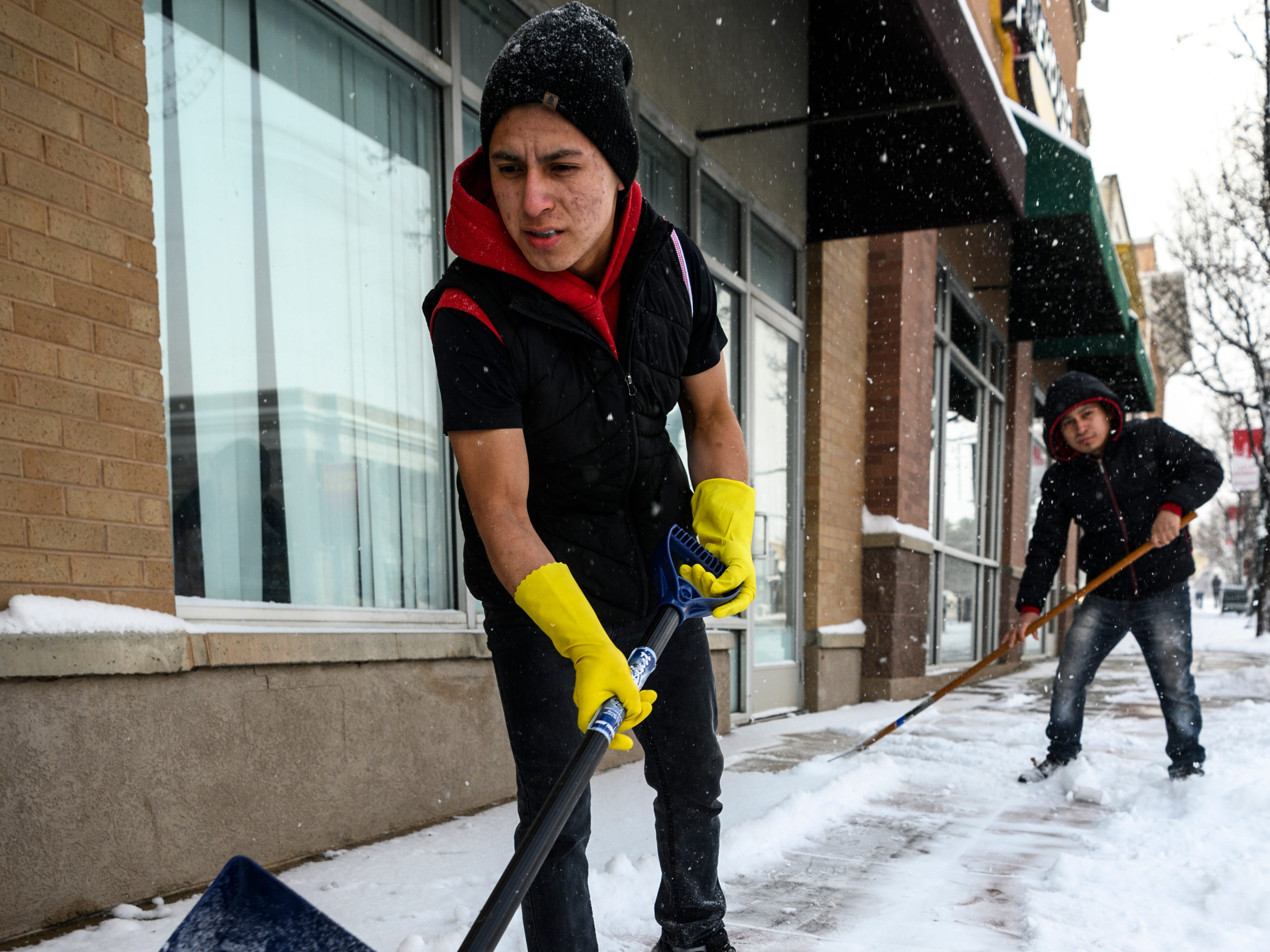 Nelson Chavez shovels snow outside a restaurant on Cedar City's Main Street Friday, December 28, 2018.