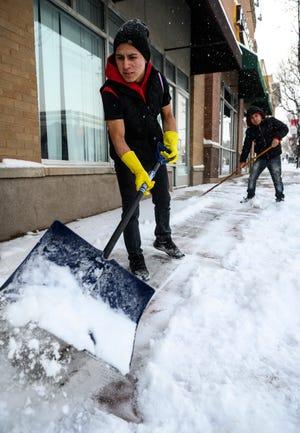 Nelson Chavez shovels snow outside a restaurant on Cedar City's Main Street Friday, December 28, 2018.
