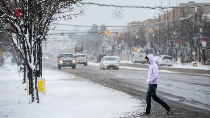 A man crosses the street in snowy Cedar City Friday, December 28, 2018.
