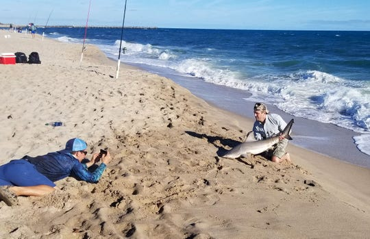 Donald Trump Jr. (right) poses for a picture with a shark taken by Josh Jorgensen, aka BlacktipH, while fishing Wednesday, Dec. 26, 2018, about a mile south of the Sebastian Inlet.
