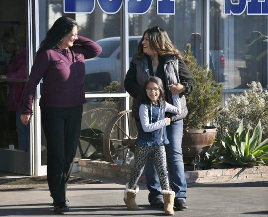 Lisa Colburn and Vera Castillo walk toward a new car on Friday, Dec. 28.