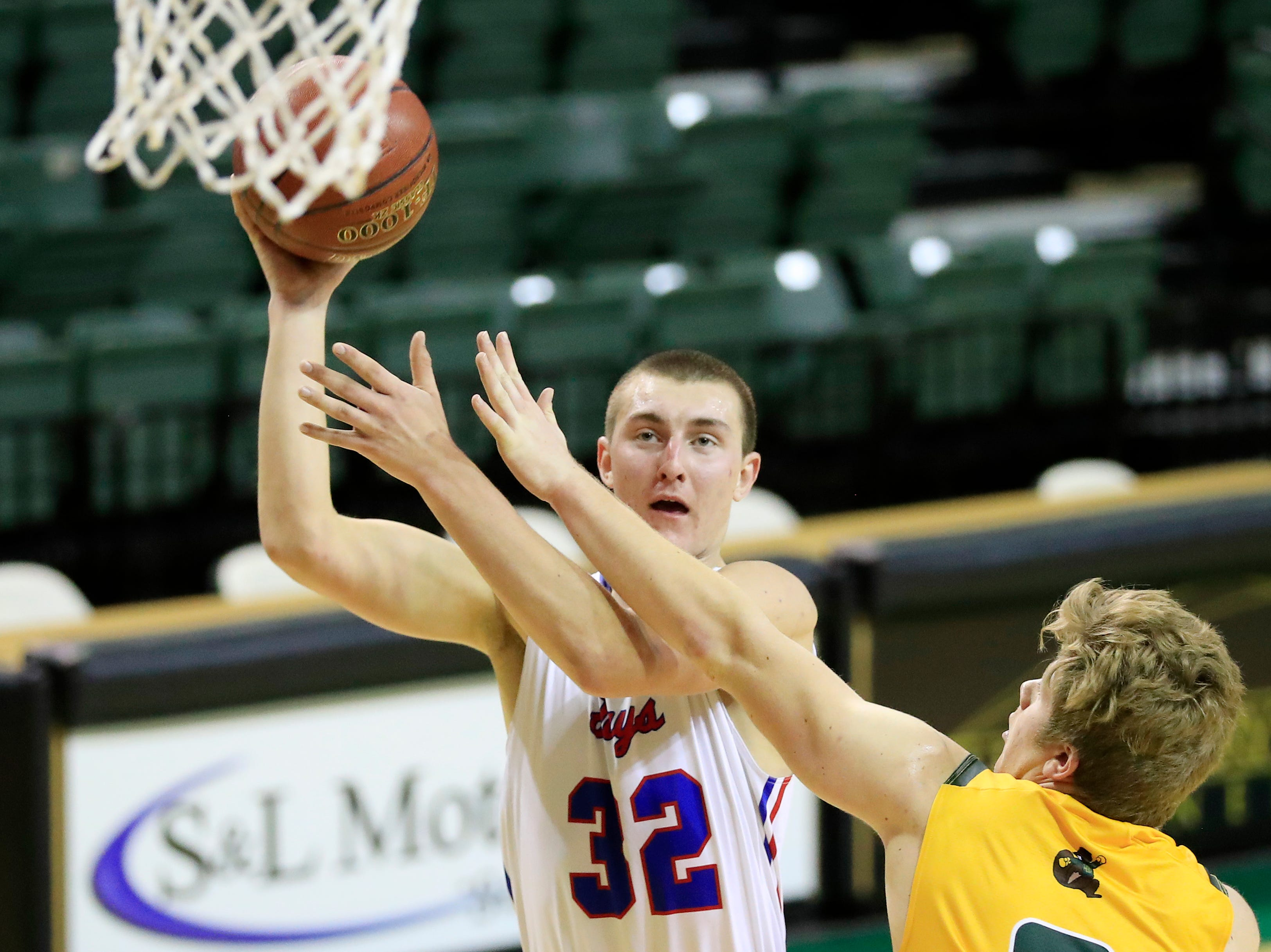 Merrill's Caleb Timm (32) shoots against Beaver Dam's Broden Boschert (2) at the Shawano Shootout at the Kress Center on Friday, December 28, 2018 in Green Bay, Wis.