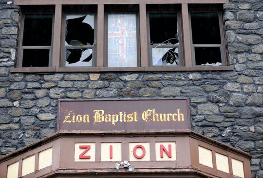 Firefighters saved the center stained-glass window depicting a cross at the Zion Evangelical Baptist Church in New Rochelle as a fire tore through the church Thursday.