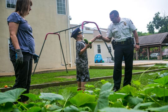 James Apostoledes, 9, gets a fist bump from Wilmington Police Lt. Dan Selekman as he helps pick vegetables in the garden at YWCA Delaware's Home-Life Management Center.