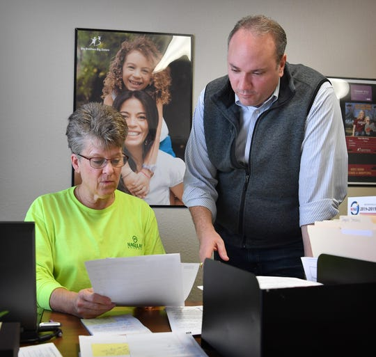Dwayne Bivona, executive director of Big Brothers Big Sisters of Wichita County, talks with recruitment manager Vicki McCann in the organization's offices.