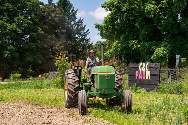 Cheu Vang of Vang C&C Farm drives a tractor.