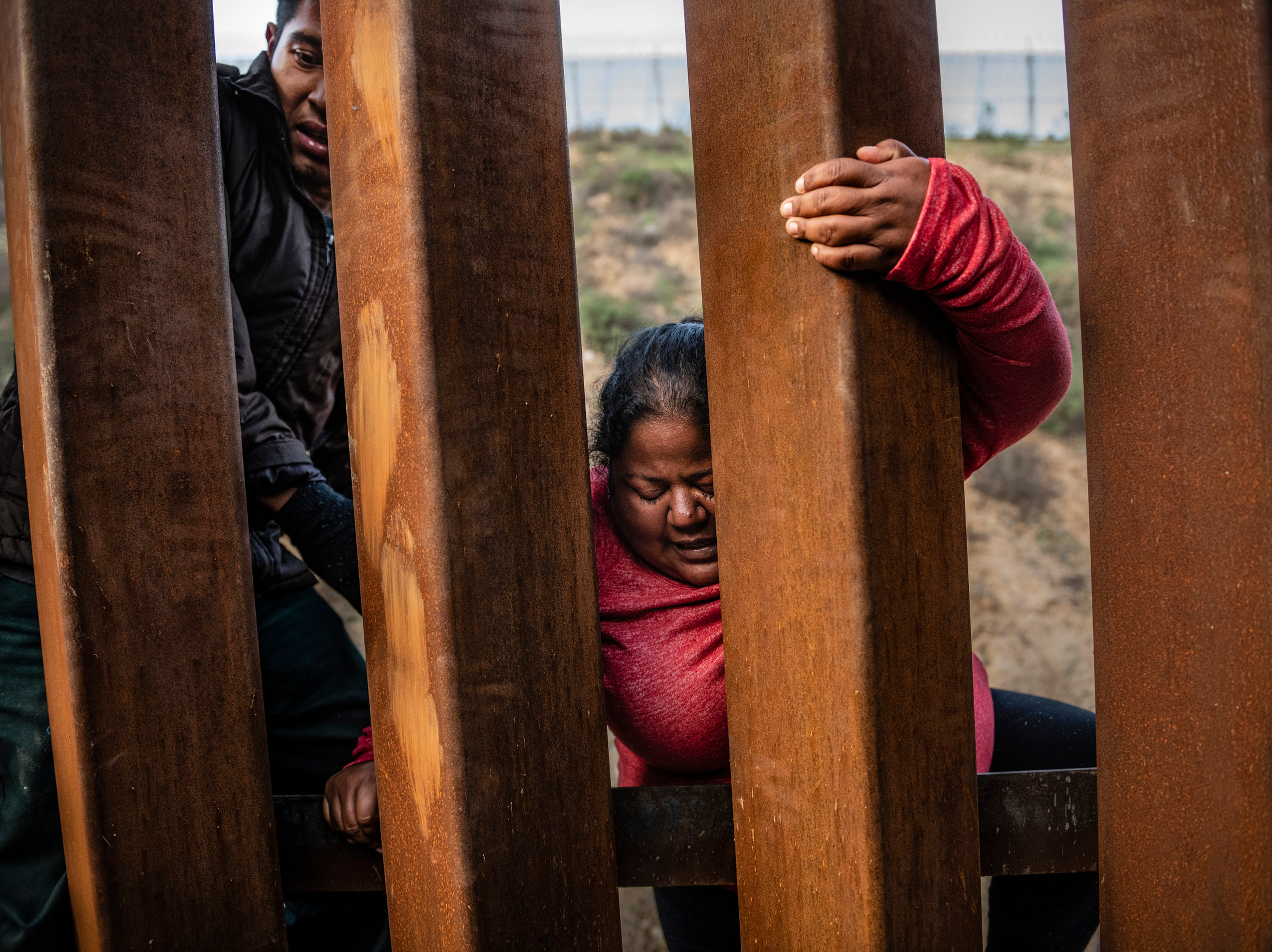 A migrant climbs the border fence before jumping into the U.S. to San Diego, Calif., from Tijuana, Mexico, Thursday, Dec. 27, 2018.