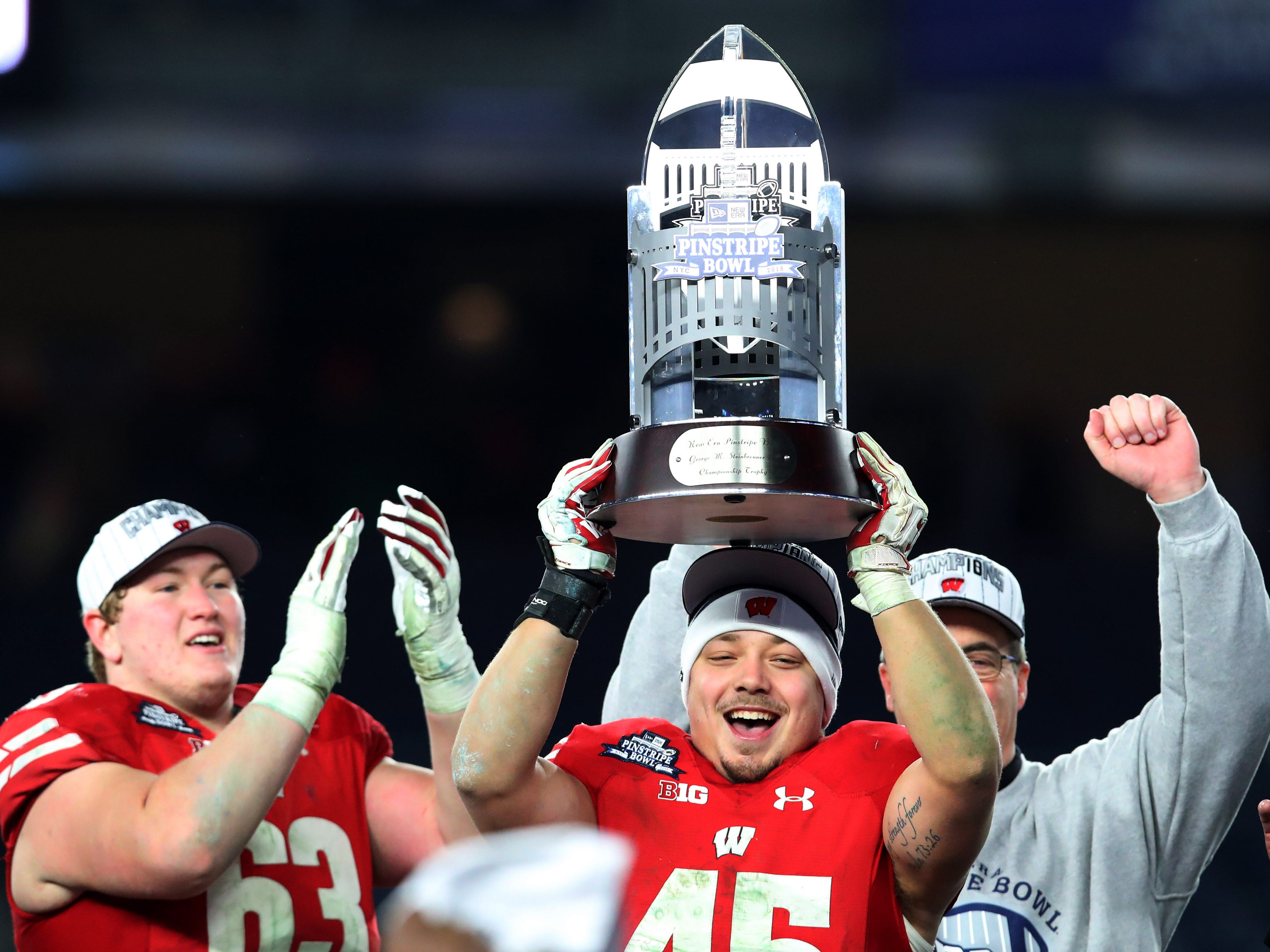 Wisconsin fullback Alec Ingold (45) holds up the 2018 Pinstripe Bowl trophy following a 35-3 win over Miami  at Yankee Stadium.