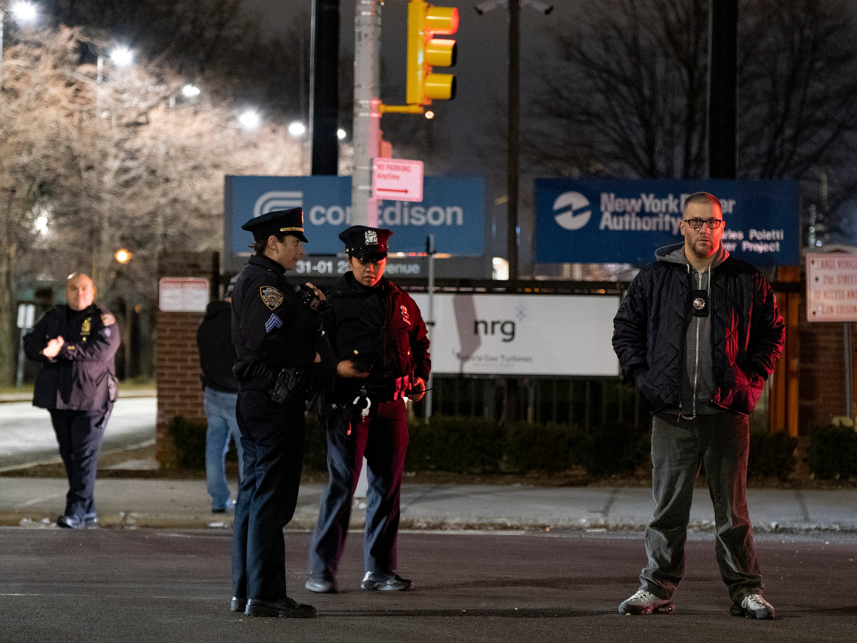 Law enforcement personnel stand in front of a Con Edison facility in the Queens borough of New York, Thursday, Dec. 27, 2018, where an earlier transformer explosion lit up the night sky for several minutes. (AP Photo/Craig Ruttle) ORG XMIT: NYCR103