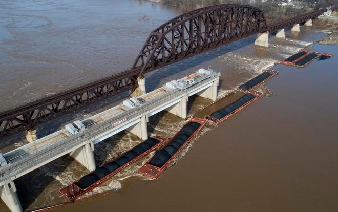 In this Dec. 26, 2018 photo, a group of loose barges are stuck at a dam on the Ohio River near Louisville, Ky. Multiple coal barges sank in the Ohio River Wednesday after they broke loose from their tugboat when one hit a bridge. (Alton Strupp/Courier Journal via AP)