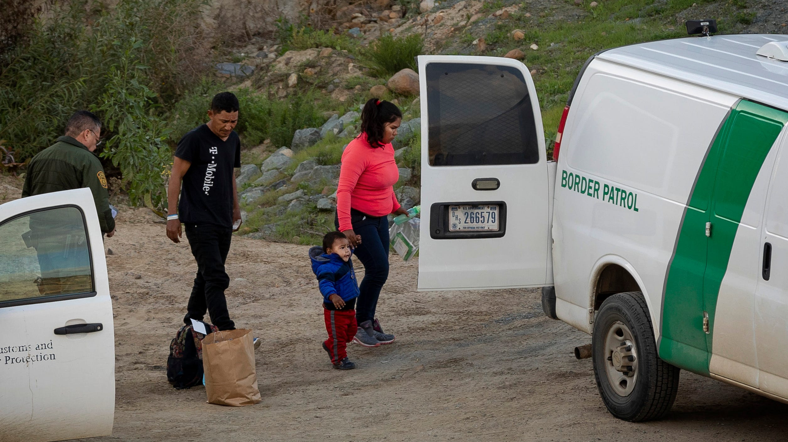 A family of asylum-seekers are taken into custody by U.S. Border Patrol agents after they crossed the U.S. border wall into San Diego, as seen from Tijuana, Mexico, Thursday, Dec. 27, 2018.