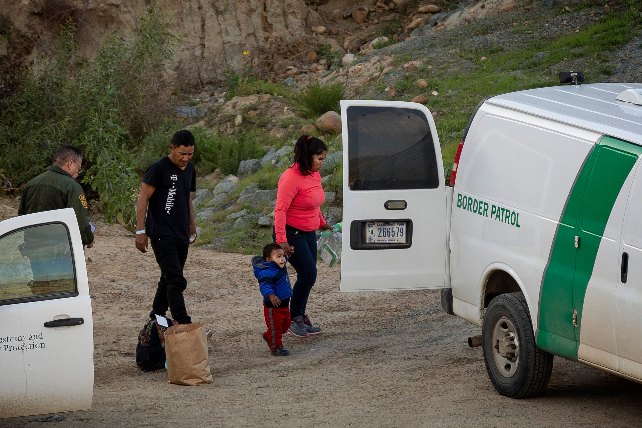 A family of asylum-seekers are taken into custody by U.S. Border Patrol agents after they crossed the U.S. border wall into San Diego, as seen from Tijuana, Mexico, on Thursday, Dec. 27, 2018.