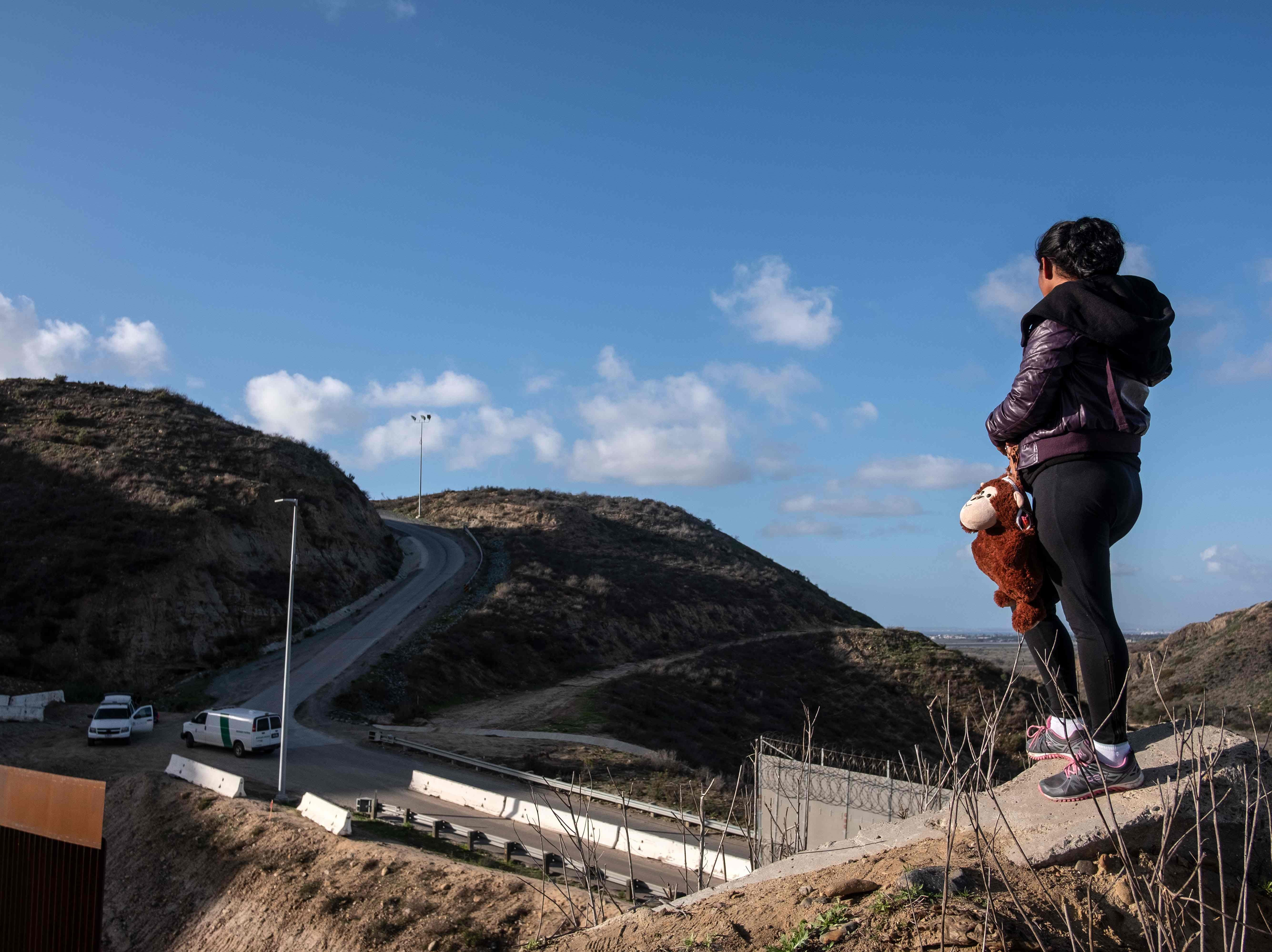 """A Central American migrant stands on the US-Mexico border fence as some try to cross from Tijuana in Mexico to San Diego County in the US, as seen from Tijuana, Baja California State, Mexico, on Dec. 27, 2018.  America's border security head warned Wednesday officials were overwhelmed by the """"enormous flow"""" of families crossing from Mexico, appealing for federal health care funding after the second child in a month died in custody."""