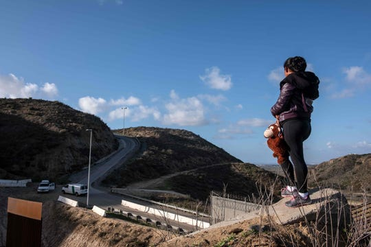 A Central American migrant stands on the U.S.-Mexico border fence as some try to cross from Tijuana in Mexico to San Diego County in the US, as seen from Tijuana, Baja California State, Mexico, on Dec. 27, 2018.