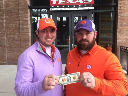 Clemson fans and brothers Tyler and Garrett Sloan hold up one of the $2 bills they brought to Dallas for purchases, following a tradition that is meant to show the cities what kind of impact visiting Clemson fans have on their economies. They're pictured at Texas Live! in Arlington ahead of the Cotton Bowl on Saturday, Dec. 29, 2018.