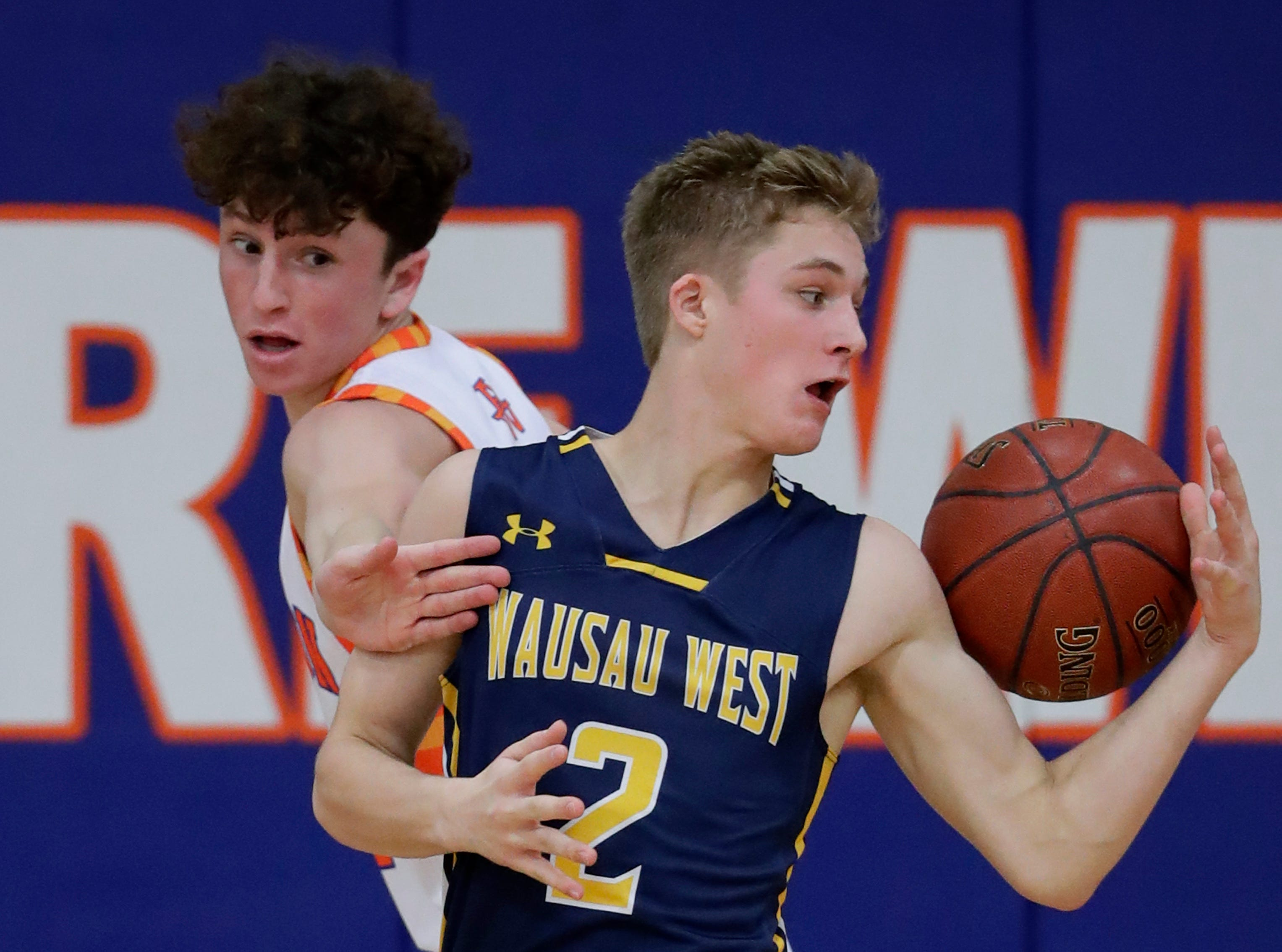 Appleton West  High School's Will Mahoney (21) defends against Wausau West High School's Mitchell Zahurones (2) during their boys basketball game Friday, December 28, 2018, in Appleton, Wis. 