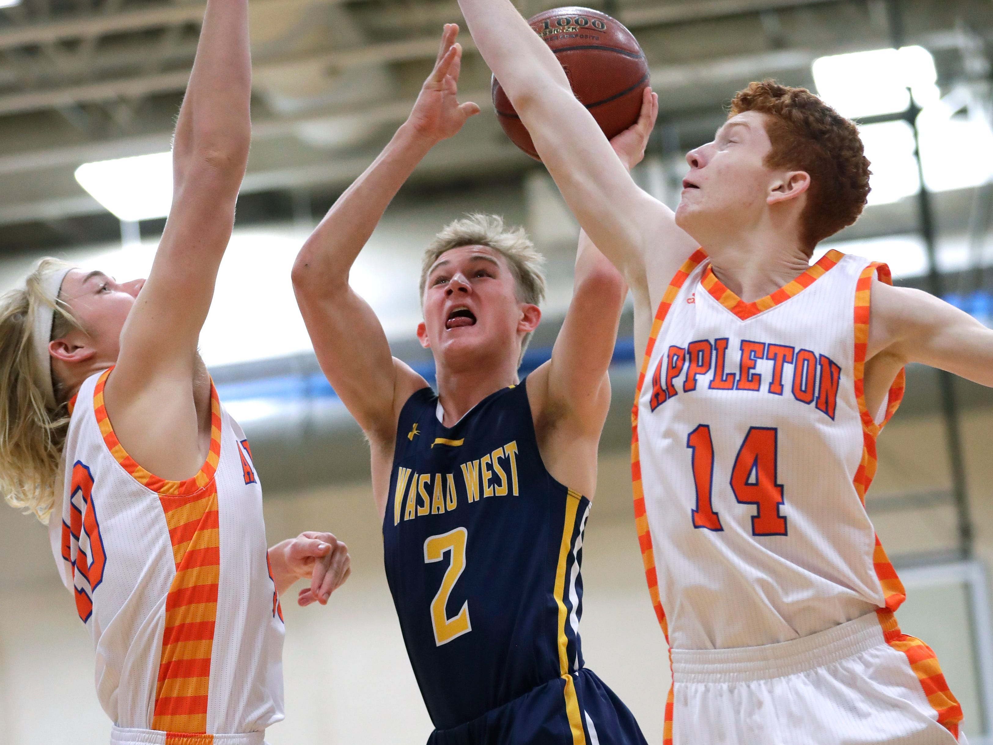 Appleton West  High School's Carson Hacker (40) and Colin Murray (14) defend against Wausau West High School's Mitchell Zahurones (2) during their boys basketball game Friday, December 28, 2018, in Appleton, Wis. Dan Powers/USA TODAY NETWORK-Wisconsin