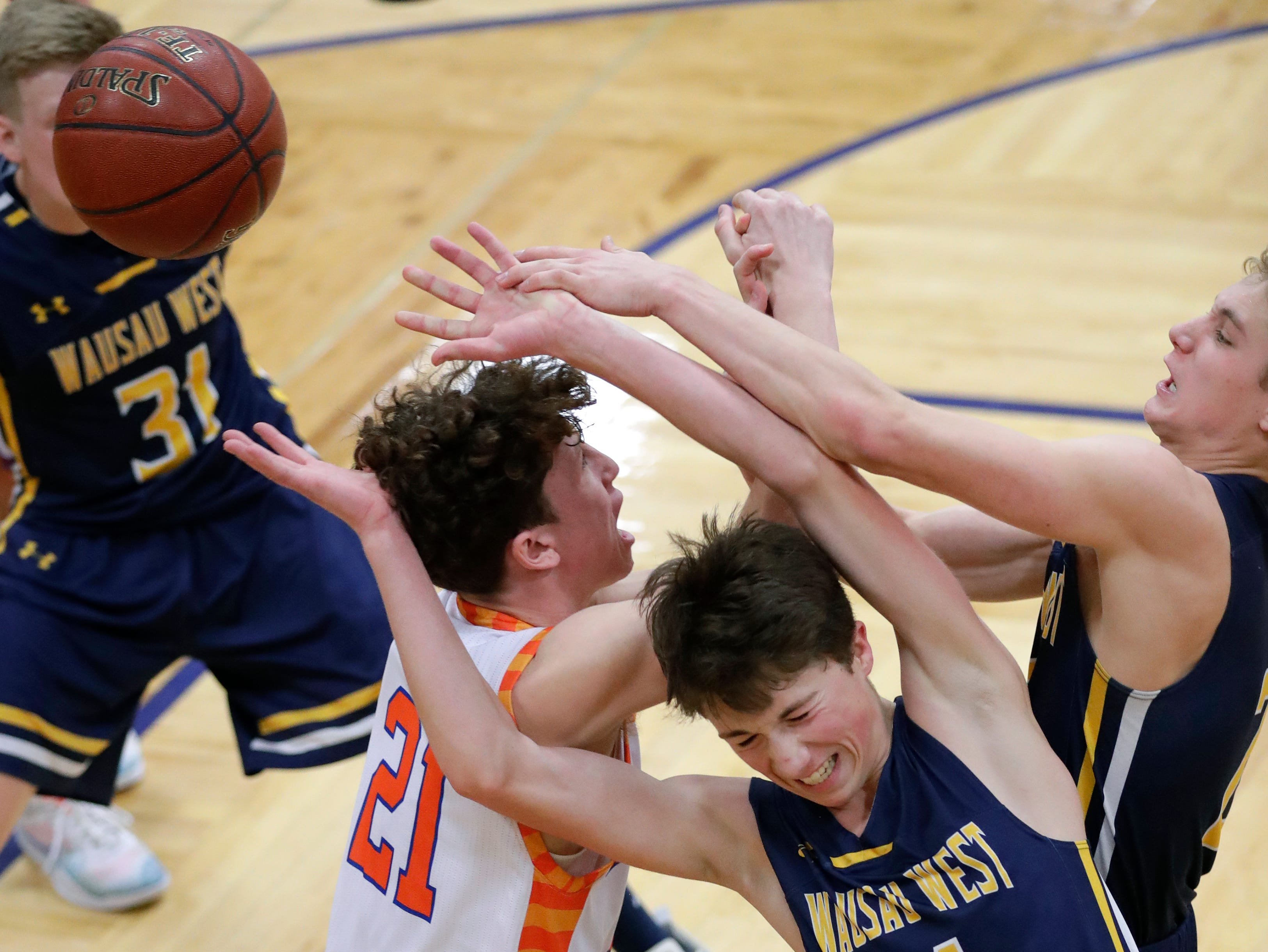 Appleton West  High School's Will Mahoney (21) battles for a rebound against Wausau West High School's Tim Deloye (11) and Mitchell Zahurones (2) during their boys basketball game Friday, December 28, 2018, in Appleton, Wis. Dan Powers/USA TODAY NETWORK-Wisconsin