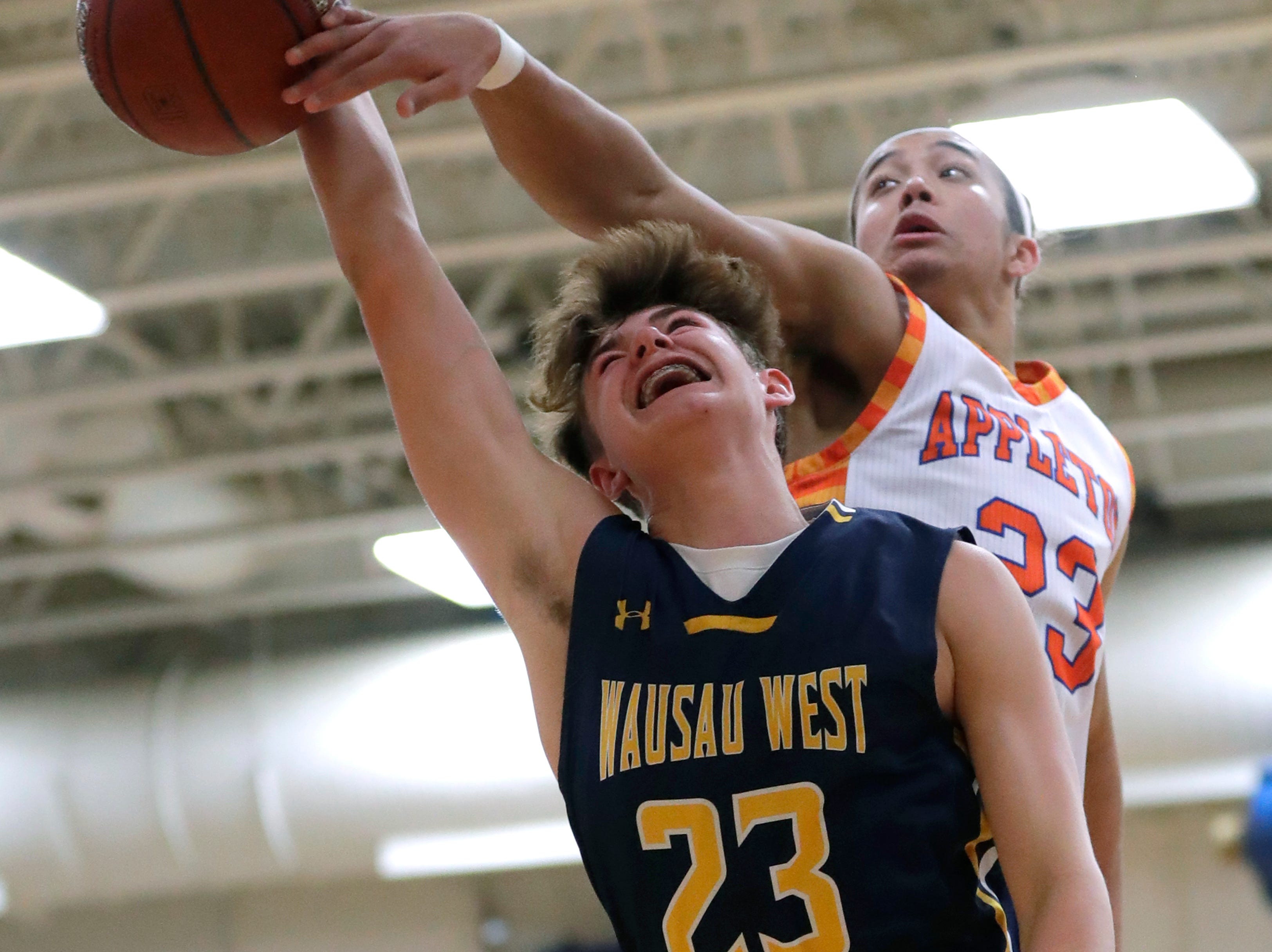 Appleton West  High School's Bubba Thompson (23) fouls Wausau West High School's Logan White (23) as he puts up a shot during their boys basketball game Friday, December 28, 2018, in Appleton, Wis. Dan Powers/USA TODAY NETWORK-Wisconsin