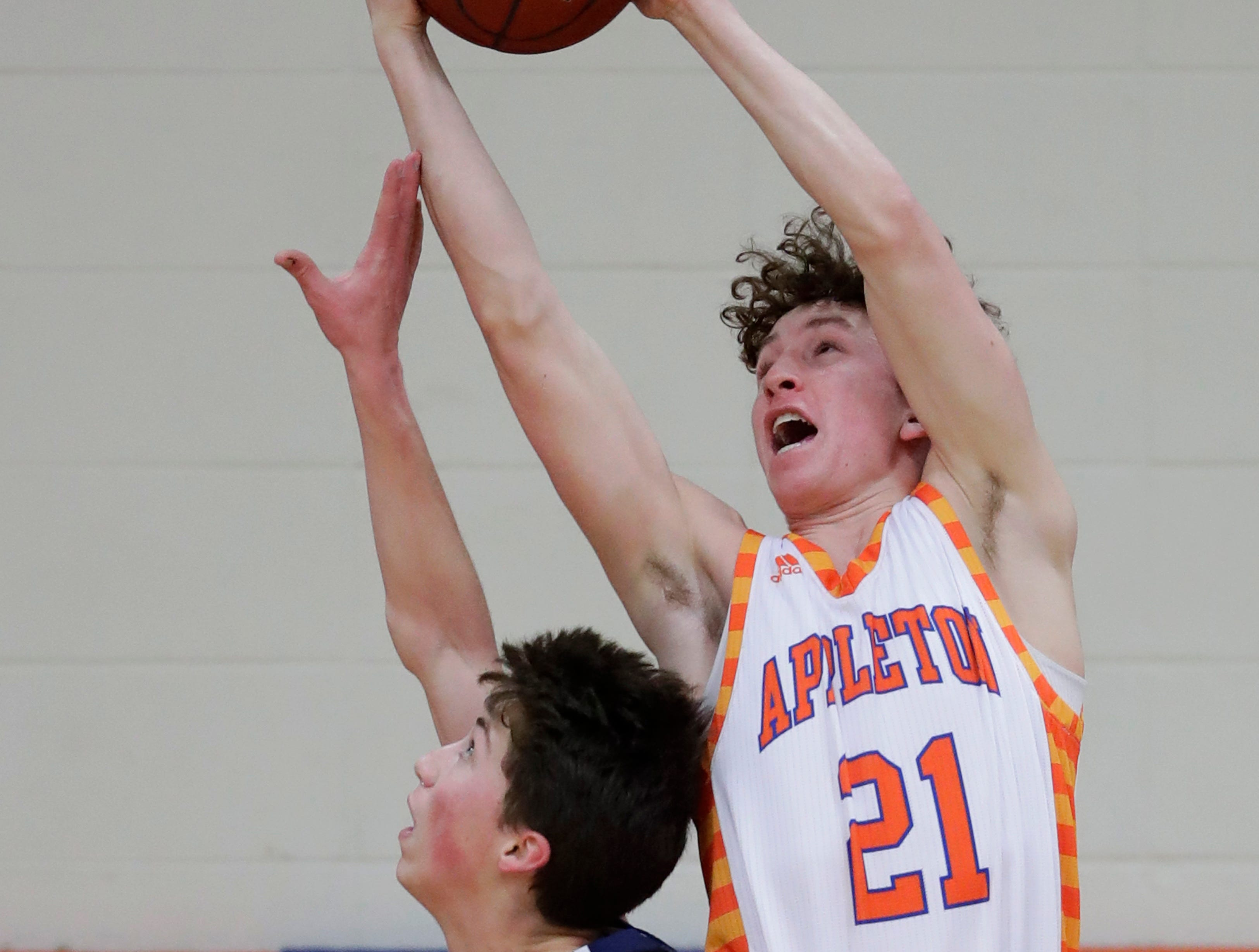 Appleton West  High School's Will Mahoney (21) pulls down a rebound against Wausau West High School's Tim Deloye (11) during their boys basketball game Friday, December 28, 2018, in Appleton, Wis. Dan Powers/USA TODAY NETWORK-Wisconsin