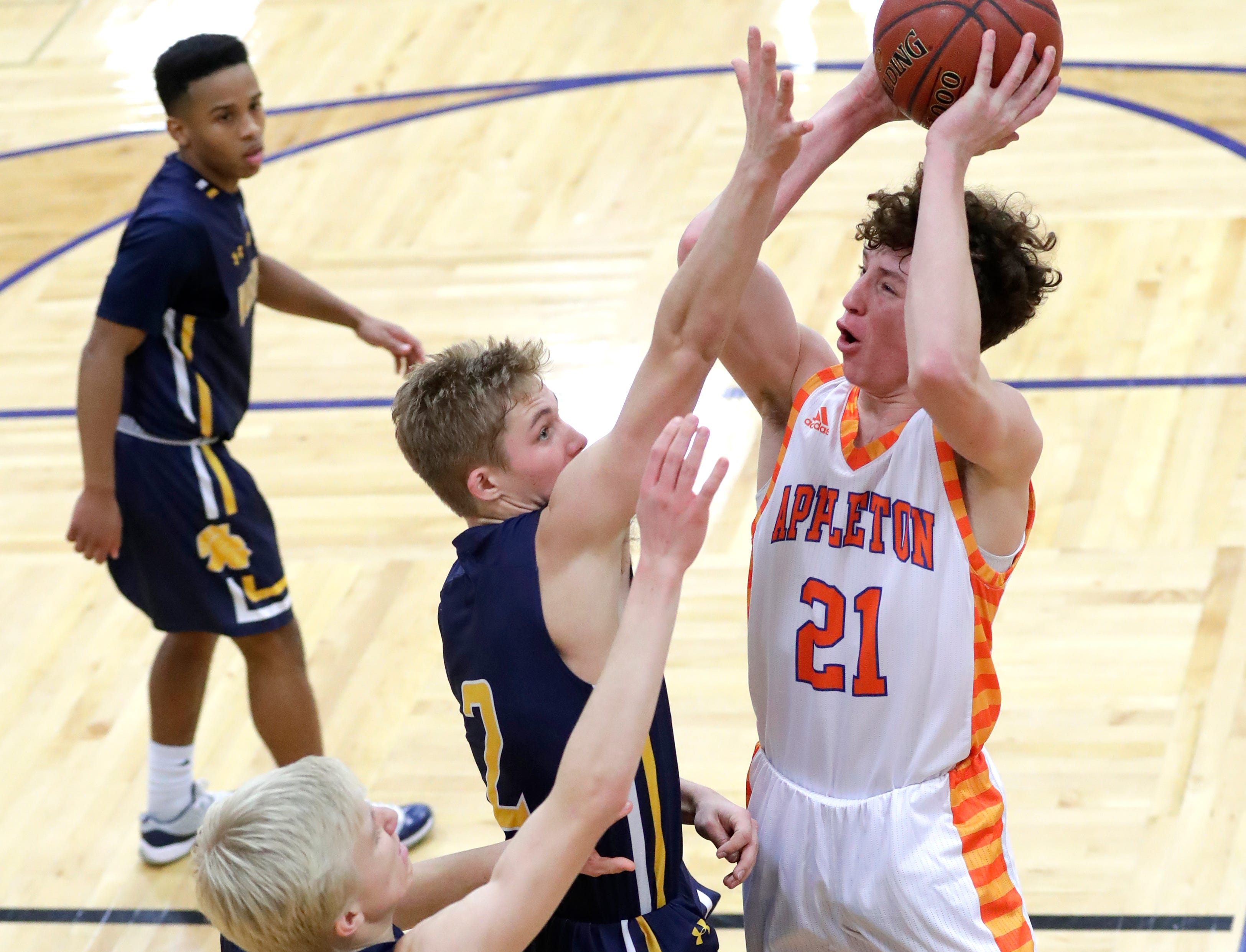 Appleton West  High School's Will Mahoney (21) puts up a shot against Wausau West High School's Ryan Hartman (21) and Mitchell Zahurones (2) during their boys basketball game Friday, December 28, 2018, in Appleton, Wis. Dan Powers/USA TODAY NETWORK-Wisconsin
