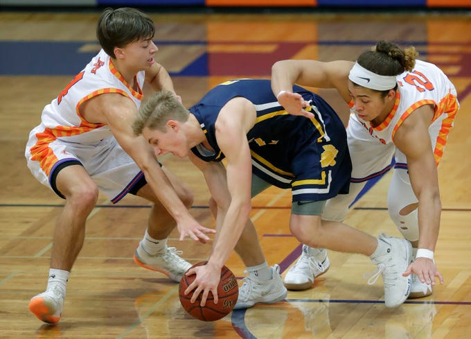 Appleton West  High School's Eli Vogel , left, and Bubba Thompson, right, defend against Wausau West High School's Mitchell Zahurones (2) during their boys basketball game Friday, December 28, 2018, in Appleton, Wis. Dan Powers/USA TODAY NETWORK-Wisconsin