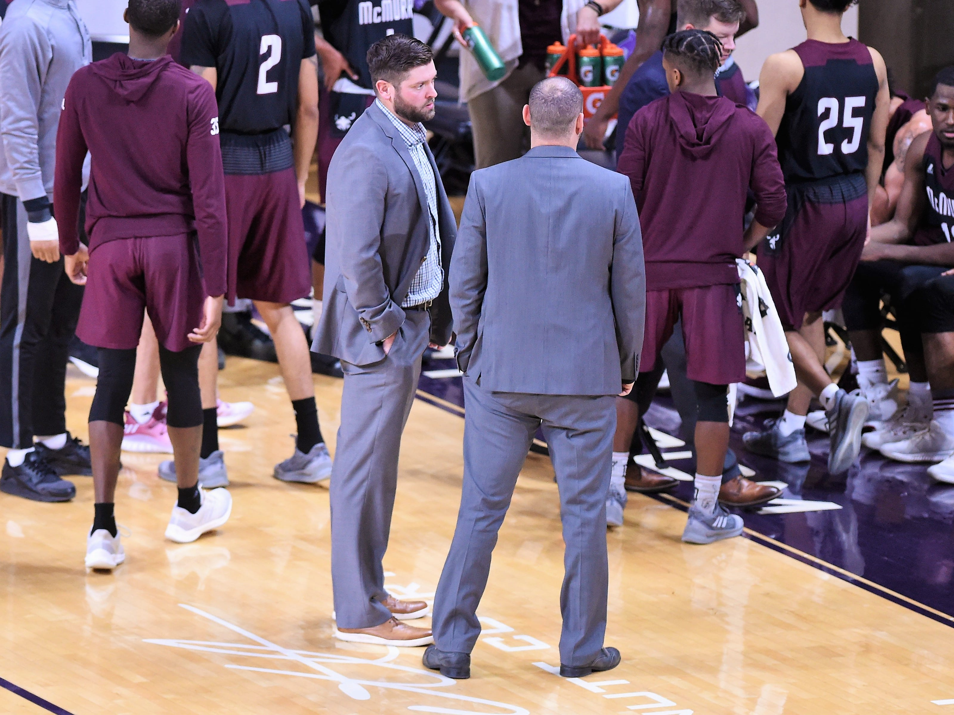 McMurry head coach Zach Pickelman, left, talks with assistant coach Rob Yeatts during a timeout against ACU on Saturday at Moody Coliseum.