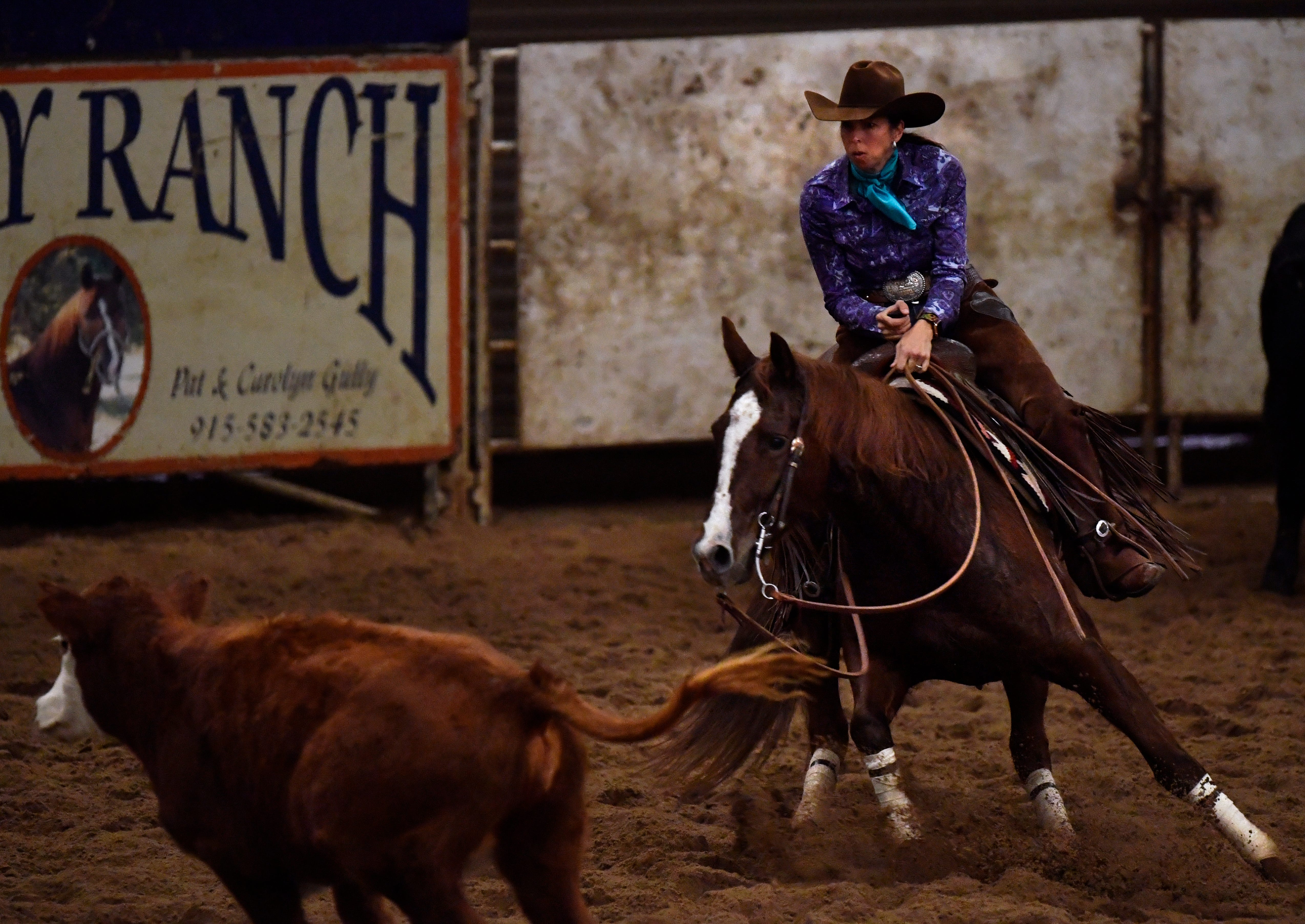 Jennifer Palmer keeps a calf from rejoining the herd Friday at the Abilene Winter Circuit Cutting in the Taylor County Coliseum.