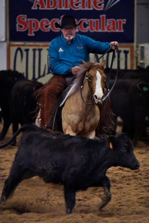 Benny Cogburn of Alto, New Mexico, keeps a calf from rejoining the herd during the Abilene Winter Circuit Cutting event Friday.